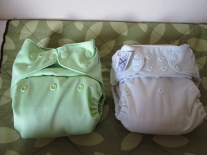 On the left: a cover stuffed with two padfolded flats. On the right: a BumGenius pocket diaper stuffed with a trifolded prefold diaper. They're snapped to  equivalent sizes.